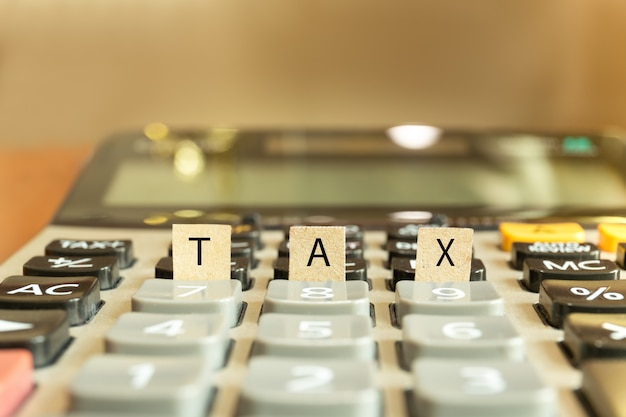 Calculator with the word tax written in paper conceptual.