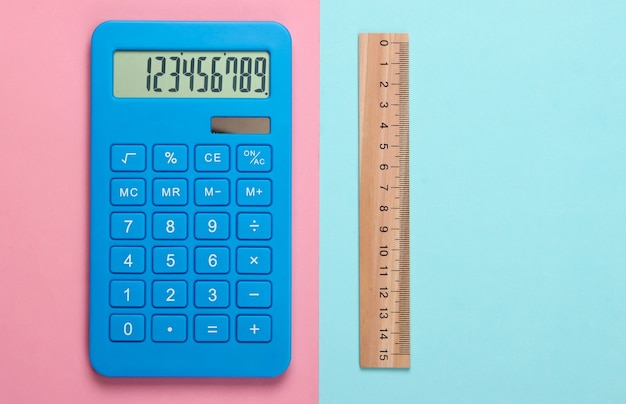 Calculator and wooden ruler on pink blue pastel. education concept
