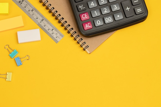 Calculator and writing equipment on yellow background