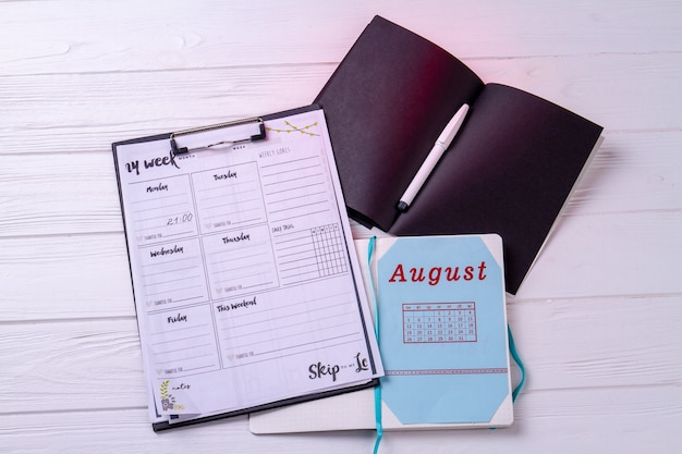 Caledars with week and august month on white desk.