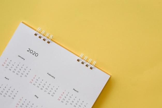 仕事と生活の概念を計画するための黄色の背景にカレンダー2020ヶ月