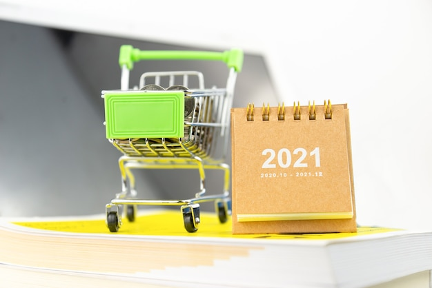 Calendar 2021 and mini shopping cart with coin in the cart on book with screen background. financial, business, shopping, knowledge concept.