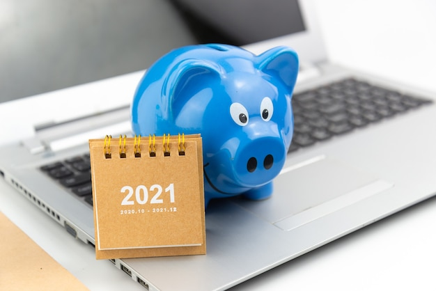 Calendar 2021 with blue piggy bank on laptop with white floor . finance savings and money wealth concept. business shopping concept.