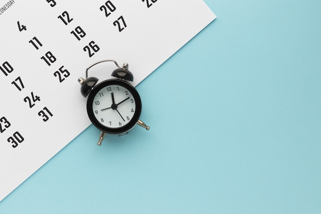 달력 및 파란색 배경에 알람 시계입니다. 마감일, 비즈니스 회의 또는 여행 계획 개념 계획. 복사 공간이있는 평면 위치, 평면도.