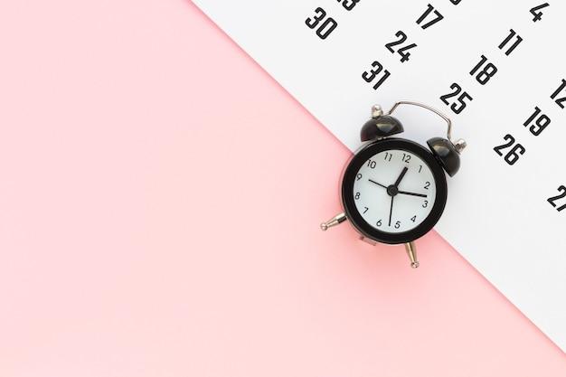 달력 및 분홍색 배경에 알람 시계입니다. 마감일, 비즈니스 회의 또는 여행 계획 개념 계획. 복사 공간이있는 평면 위치, 평면도.