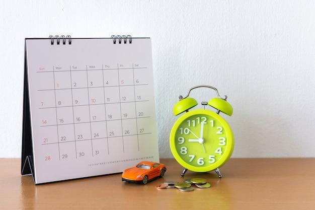 Календарь и автомобиль на столе. день покупки или продажи автомобиля или оплаты аренды или кредита или ремонта