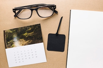 Calendar and glasses near notebook