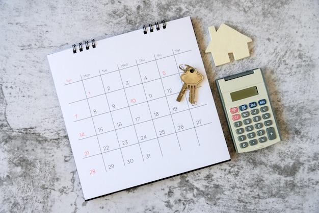 カレンダーとテーブルの上の家。家の売買、家賃やローンの支払いの日。
