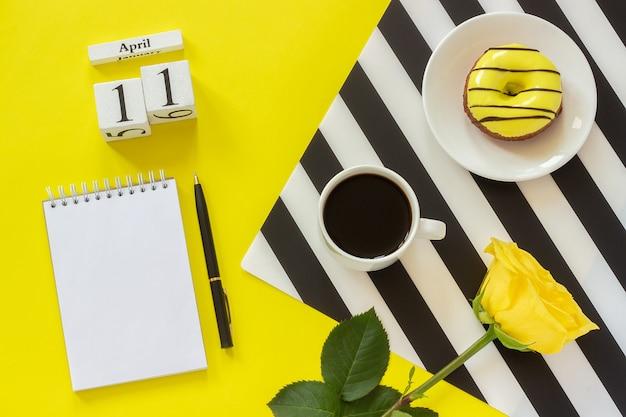 カレンダー4月11日。一杯のコーヒー、ドーナツ、バラ、メモ帳。コンセプトスタイリッシュな職場