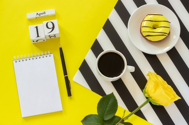 Calendar april 19th. cup coffee, donut and rose,  notepad on yellow background. concept stylish workplace