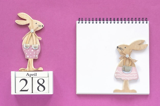 Calendar april 28, pair wooden easter bunnies, white notepad. christian easter