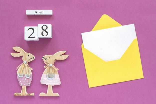 Календарь 28 апреля, пара деревянных пасхальных кроликов, желтый конверт с пустой картой на фиолетовом фоне бумаги.