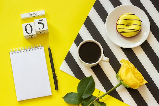 Calendar april 5th. cup of coffee, yellow donut and rose, empty open notepad