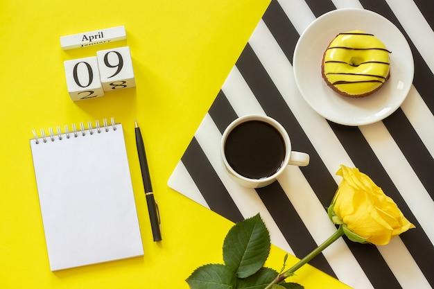 Calendar april 9th. cup of coffee, donut and rose, notepad on yellow background.