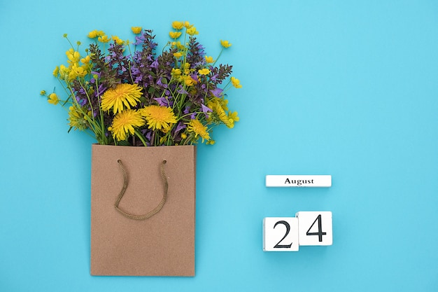 Calendar august 24 and field colorful rustic flowers in craft package on blue background. greeting card flat lay