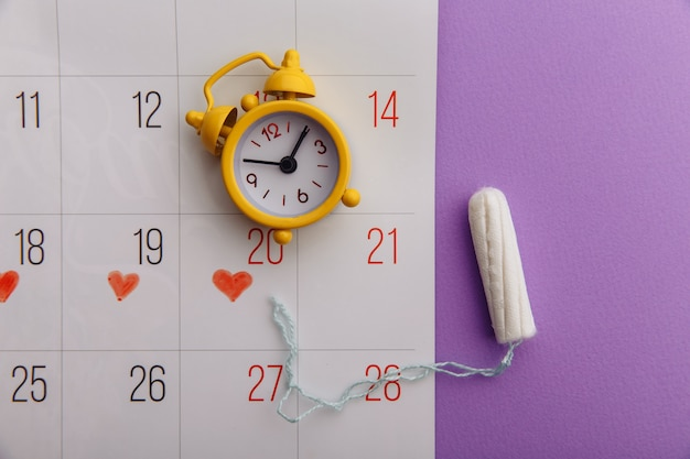 ライラックの背景にカレンダー、綿タンポン、黄色の目覚まし時計。女性の月経周期の概念。