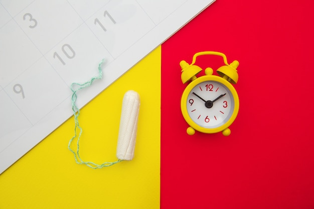 Calendar, cotton tampon and yellow alarm clock on colorful