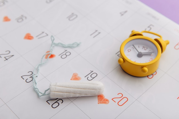 Calendar, cotton tampon and yellow alarm clock on lilac background close-up.
