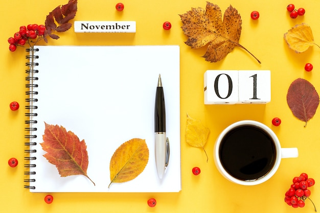 Calendar date, cup of coffee, notepad, berries with pen and autumn leaves