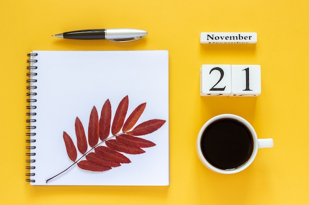 Calendar date, cup of coffee, notepad with pen and autumn leaves