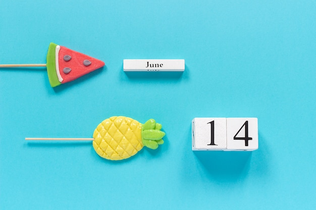Calendar date june 14th and summer fruits candy pineapple, watermelon lollipops.