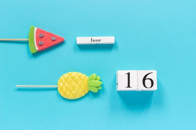 Calendar date june 16th and summer fruits candy pineapple, watermelon lollipops.