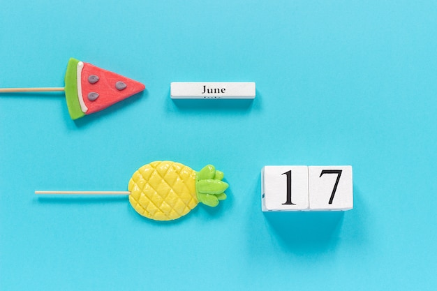 Calendar date june 17th and summer fruits candy pineapple, watermelon lollipops.