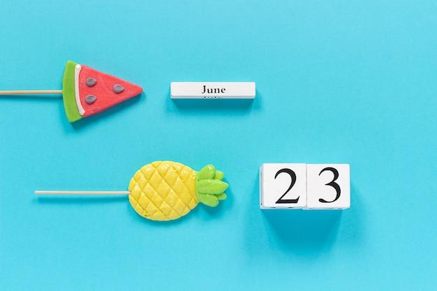 Calendar date june 23rd and summer fruits candy pineapple, watermelon lollipops