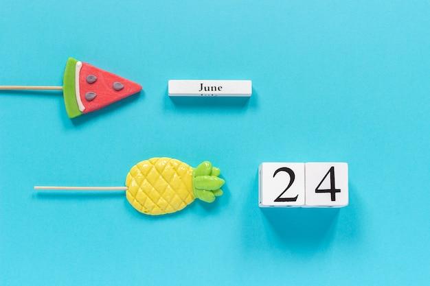 Calendar date june 24th and summer fruits candy pineapple, watermelon lollipops.