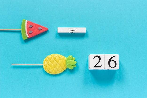 Calendar date june 26th and summer fruits candy pineapple, watermelon lollipops