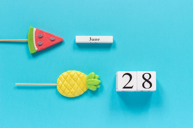 Calendar date june 28th and summer fruits candy pineapple, watermelon lollipops