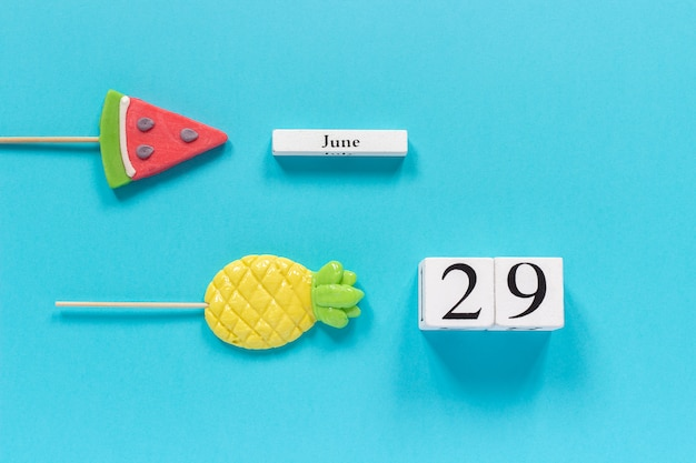 Calendar date june 29th and summer fruits candy pineapple, watermelon lollipops.