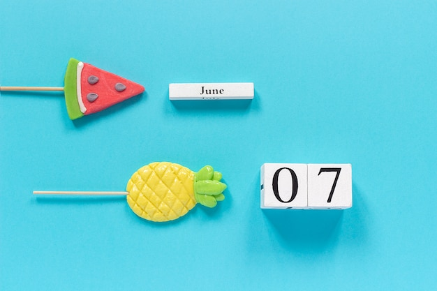 Calendar date june 7th and summer fruits candy pineapple, watermelon lollipops