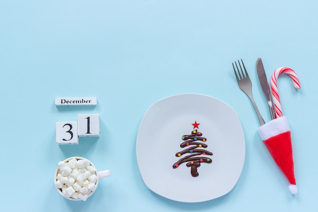 Calendar december 31st. sweet chocolate christmas tree on plate, cutlery, cup of cocoa