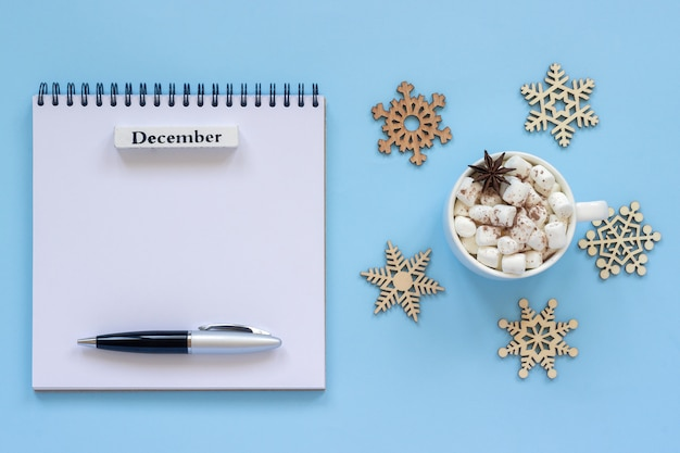 Calendar december and cup of cocoa with marshmallow, empty open notepad