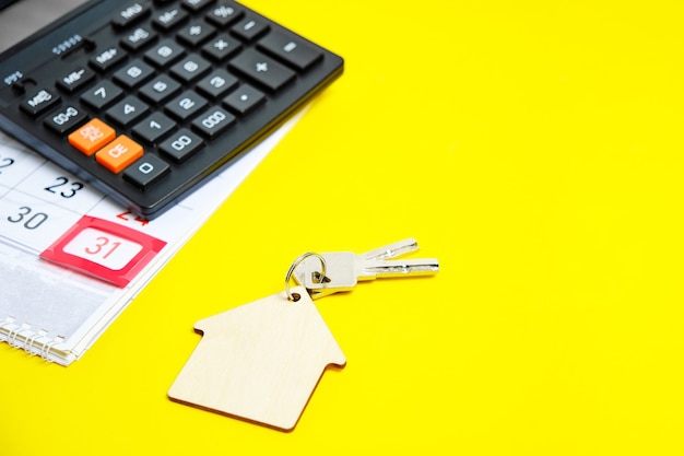 カレンダー月末の電卓黄色の背景の家やアパートの鍵コンセプトアパートの購入新年の贈り物