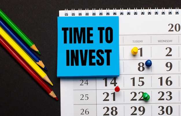 The calendar has light blue note paper with the text time to invest. nearby colored pencils on a dark background. view from above