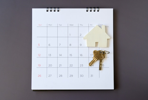 Calendar and house on table. day of buying or selling a house or payment for rent or loan.