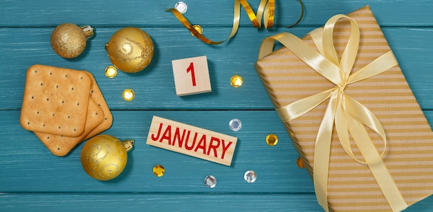 Calendar january 1st, golden christmas decorations, gift box and crackers