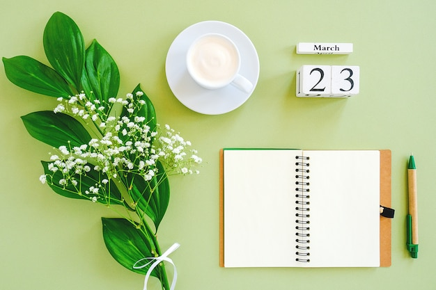 Calendar march 23. notepad, cup of coffee, bouquet flowers on green background.