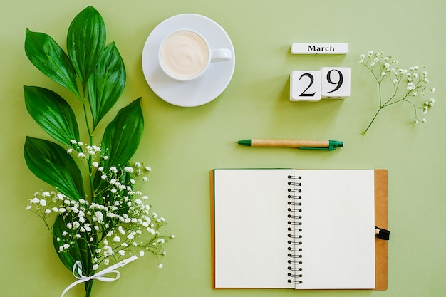 Calendar march 29. notepad, cup of coffee, bouquet flowers on green background. concept hello spring
