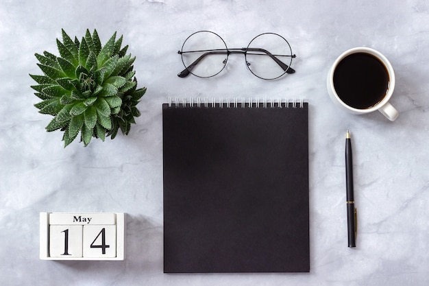 Calendar may 14. black notepad, cup of coffee, succulent, glasses on marble