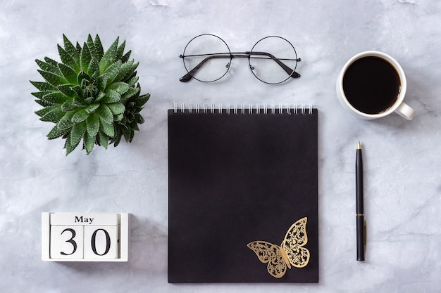 Calendar may 30. black notepad, cup of coffee, succulent, glasses on marble