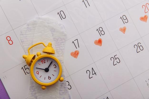 Календарь, менструальные прокладки и крупный план желтого будильника.