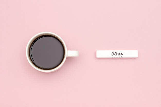 Calendar month may and cup of black coffee on pastel pink paper background.