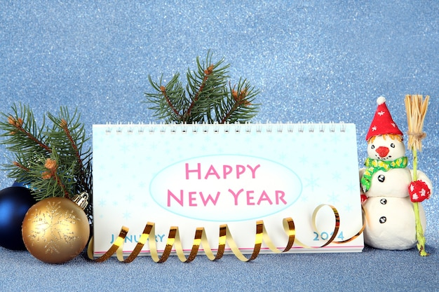 Календарь, новогодний декор и елка на синем фоне