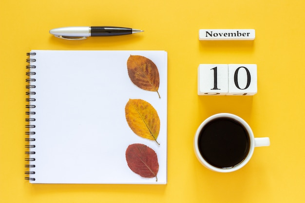 Calendar november 10 cup of coffee, notepad with pen and yellow leaf on yellow background
