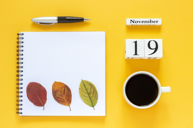 Calendar november 19 cup of coffee, notepad with pen and yellow leaf on yellow background