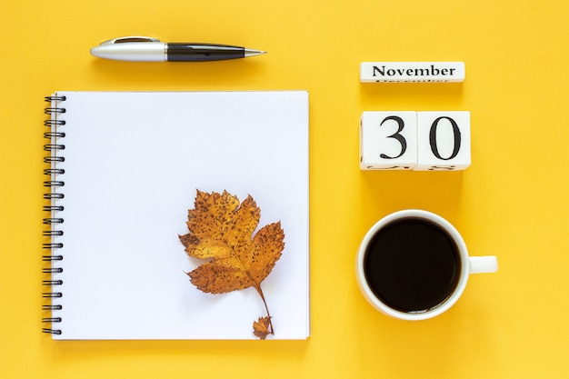 Calendar november 30 cup of coffee, notepad with pen and yellow leaf on yellow background