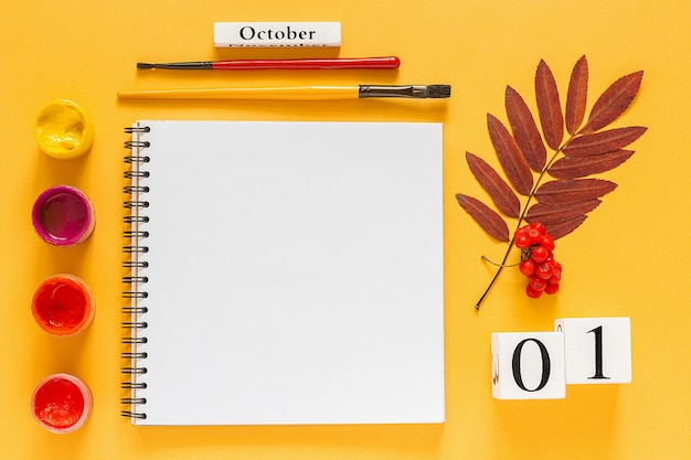 Calendar october 1, open notepad, autumn colored leaves and watercolor paints on yellow background.